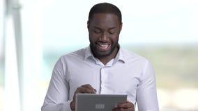 Hombre de negocios de piel morena atractivo usando la tableta de la PC almacen de video