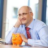 Hombre de negocios With Piggybank Looking lejos en el escritorio Foto de archivo