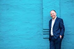 Hombre de negocios positivo que se inclina en la pared de la turquesa Fotografía de archivo
