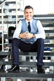 Hombre de negocios positivo que se sienta en las escaleras de la oficina moderna Imagenes de archivo
