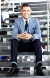 Hombre de negocios positivo que se sienta en las escaleras de la oficina moderna Fotos de archivo libres de regalías
