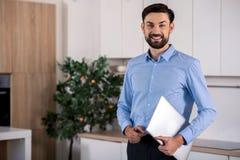 Hombre de negocios positivo que sostiene su ordenador portátil imagen de archivo libre de regalías