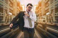 Hombre de negocios de precipitación que corre o que compite con con tiempo imagen de archivo libre de regalías