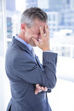 Hombre de negocios preocupado que lleva a cabo su cabeza Imagen de archivo