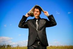 Hombre de negocios preocupante con la carpeta sobre su cabeza Imagenes de archivo