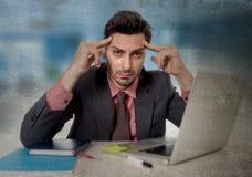 Hombre de negocios preocupante en el dolor de cabeza sufridor de la oficina que trabaja en el ordenador desesperado en stress lab Imágenes de archivo libres de regalías