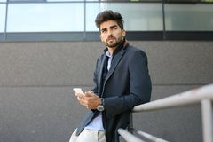 Hombre de negocios preocupante que coloca y que sostiene el teléfono elegante fotos de archivo libres de regalías