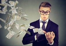 Hombre de negocios preocupante que mira su cartera con los billetes de banco del dólar del dinero que vuelan hacia fuera lejos foto de archivo