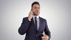 Hombre de negocios preocupante serio que habla en el teléfono móvil en fondo de la pendiente almacen de video