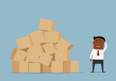 Hombre de negocios preocupante y pila grande de cajas Foto de archivo