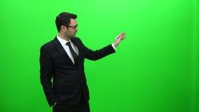 Hombre de negocios Presenting delante de una pantalla verde Lado izquierdo metrajes