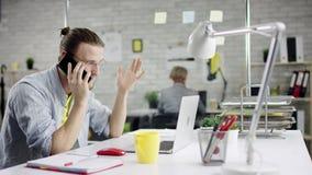 Hombre de negocios productivo que inclina el trabajo de oficina detrás de acabado en el ordenador portátil, encargado eficaz sati almacen de metraje de vídeo