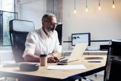 Hombre de negocios profesional adulto que lleva vidrios clásicos y que trabaja en la tabla de madera en estudio coworking moderno Imagen de archivo