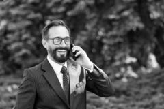 Hombre de negocios profesional feliz atractivo vestido en el traje y los vidrios que hablan en el teléfono móvil afuera en parque imagenes de archivo