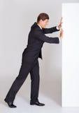 Hombre de negocios Pushing Blank Placard foto de archivo