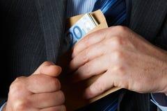 Hombre de negocios Putting Envelope Of Euros Into Jacket Pocket Foto de archivo libre de regalías