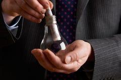 Hombre de negocios Putting Sterling Note Into Light Bulb Imagen de archivo libre de regalías