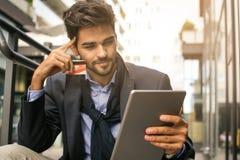 Hombre de negocios que aúlla sobre tarjeta de crédito y que usa iPod fotos de archivo