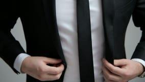 Hombre de negocios que abotona un botón en su chaqueta negra almacen de video
