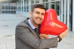 Hombre de negocios que abraza un corazón gigante fotografía de archivo