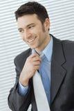 Hombre de negocios que ajusta el lazo Foto de archivo libre de regalías