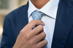 Hombre de negocios que ajusta el suyo lazo Imagen de archivo