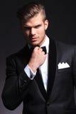 Hombre de negocios que ajusta su corbata de lazo fotografía de archivo
