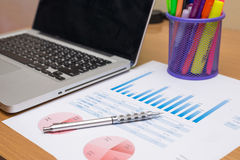Hombre de negocios que analiza cartas de la inversión con el ordenador portátil Imagen de archivo libre de regalías