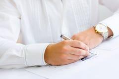 Hombre de negocios que analiza el gráfico y que hace notas Foto de archivo libre de regalías
