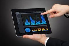 Hombre de negocios que analiza gráficos en la tableta digital Foto de archivo libre de regalías
