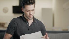 Hombre de negocios que analiza los papeles en la cocina abierta Hombre joven que trabaja en el pa?s almacen de video