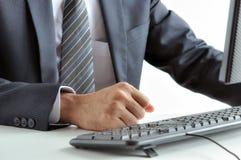 Hombre de negocios que aprieta su puño en la tabla de funcionamiento Fotografía de archivo