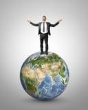 Hombre de negocios que aumenta sus manos al cielo que se coloca en el globo de la tierra Los elementos de esta imagen son suminis Foto de archivo libre de regalías