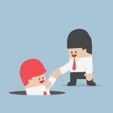 Hombre de negocios que ayuda a su amigo por la toma él hacia fuera del agujero Imágenes de archivo libres de regalías