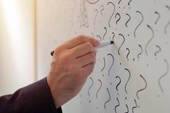 Hombre de negocios que bosqueja muchos signos de interrogación en whiteboard de la oficina foto de archivo