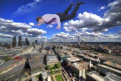 Hombre de negocios que cae abajo con la ciudad moderna adentro Imagen de archivo