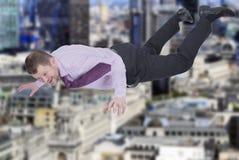 Hombre de negocios que cae abajo con la ciudad moderna adentro Imagenes de archivo
