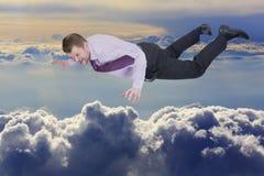 Hombre de negocios que cae abajo sobre las nubes en fondo Foto de archivo