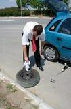 Hombre de negocios que cambia un neumático Fotos de archivo