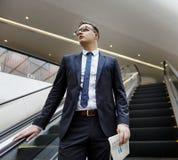 Hombre de negocios que camina abajo de concepto de la escalera móvil Fotografía de archivo libre de regalías