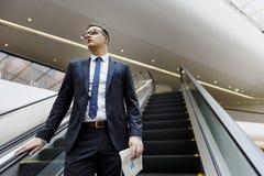 Hombre de negocios que camina abajo de concepto de la escalera móvil Imagenes de archivo