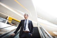 Hombre de negocios que camina abajo de concepto de la escalera móvil Fotografía de archivo
