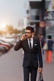 Hombre de negocios que camina abajo de la calle y que habla en el teléfono con luz del sol temprana Movimiento enmascarado Fotos de archivo libres de regalías