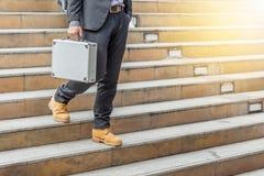 Hombre de negocios que camina abajo de las escaleras con los bolsos Foto de archivo
