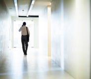 Hombre de negocios que camina abajo del pasillo en el teléfono Fotos de archivo
