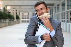 Hombre de negocios que camina, comiendo y hablando en el teléfono al mismo tiempo imágenes de archivo libres de regalías