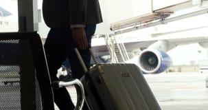 Hombre de negocios que camina con el bolso de la carretilla almacen de metraje de vídeo