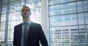 Hombre de negocios que camina con equipaje en el pasillo en la oficina 4k metrajes