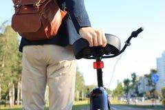 Hombre de negocios que camina con la bici en calle después de trabajo Imagenes de archivo