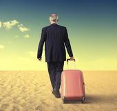 Hombre de negocios que camina con la maleta en un desierto Foto de archivo